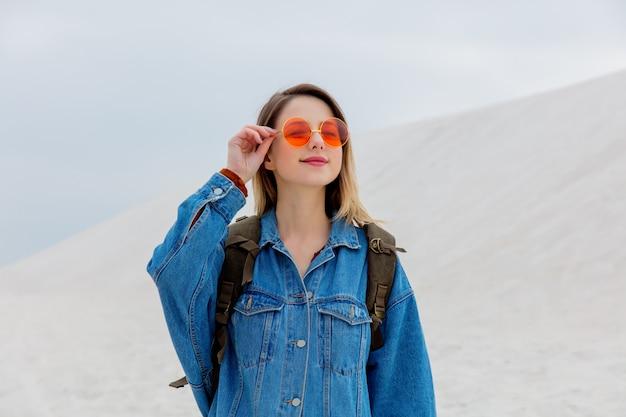 Fille de voyage avec sac à dos dans une lunette de soleil sur une plage de sable