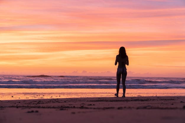 Une fille de voyage se détendre sur la plage de sable blanc au coucher du soleil