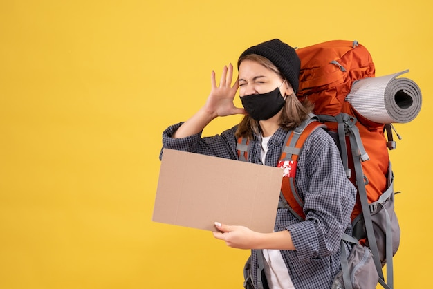 Fille de voyageur criant avec masque noir et sac à dos tenant du carton