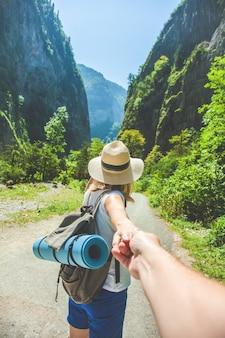 Fille voyageur dans un chapeau mène la main d'un gars sur le fond des voyageurs de la montagne