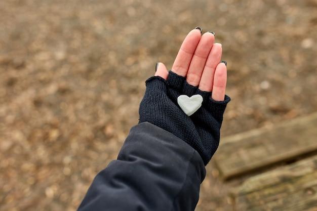Fille de voyageur dans des gants noirs garder dans la main guimauve en forme de coeur