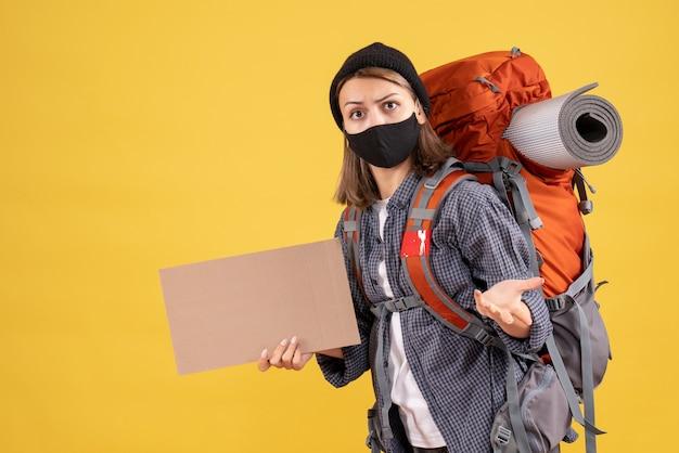 Fille de voyageur étonnée avec masque noir et sac à dos tenant du carton