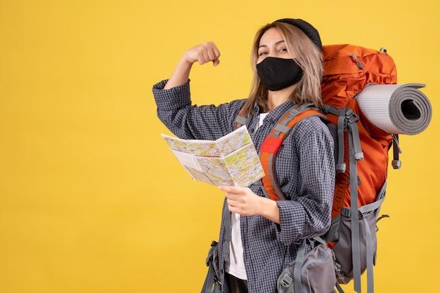 Fille de voyageur avec masque noir et sac à dos tenant une carte montrant le muscle du bras