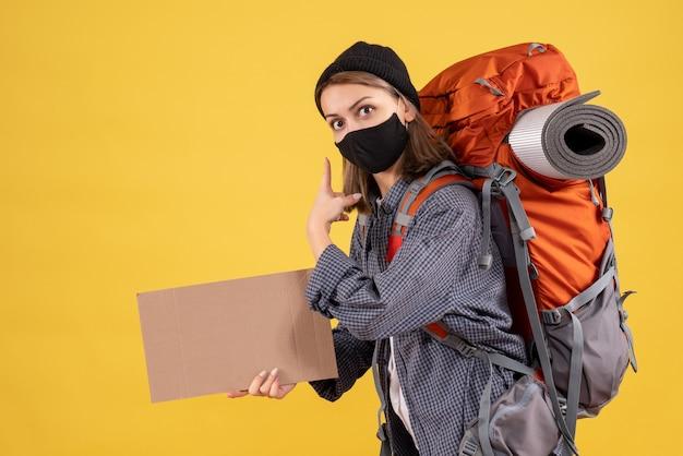 Fille de voyageur avec masque noir et sac à dos tenant un carton pointant derrière