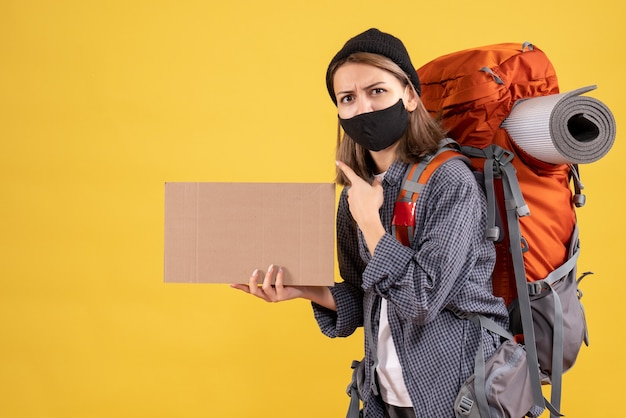 Fille de voyageur avec masque noir et sac à dos tenant du carton