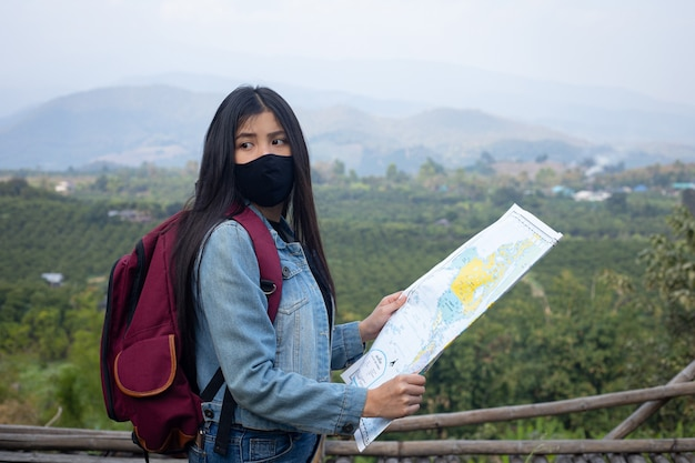 Fille de voyageur recherchant la bonne direction sur la carte