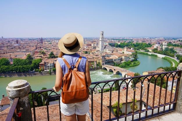 Fille de voyageur romantique visitant la ville d'amour de vérone. vue arrière d'une jeune femme routard profitant du paysage urbain de vérone, en italie.