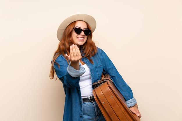Fille de voyageur rousse avec valise sur mur isolé invitant à venir avec la main. heureux que tu sois venu