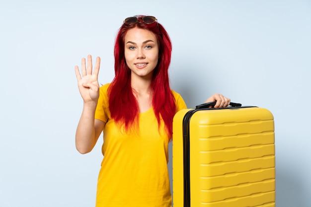 Fille de voyageur tenant une valise isolée sur fond bleu heureux et en comptant quatre avec les doigts