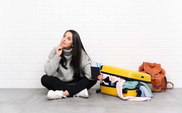 Fille de voyageur avec une valise pleine de vêtements assis sur le sol en pensant à une idée