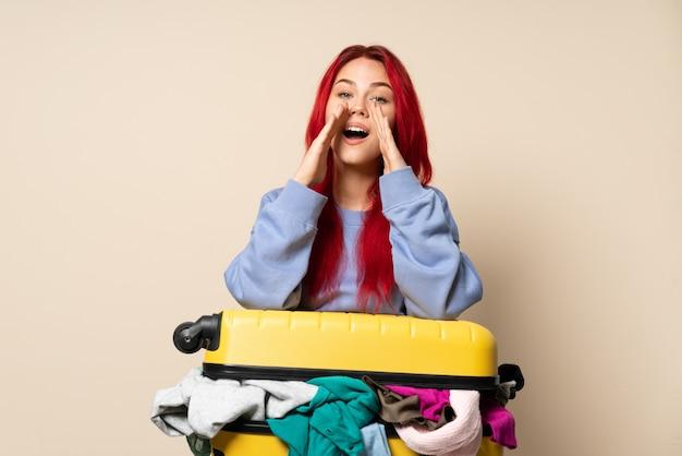 Fille de voyageur avec une valise pleine de vêtements isolé sur fond beige criant et annonçant quelque chose