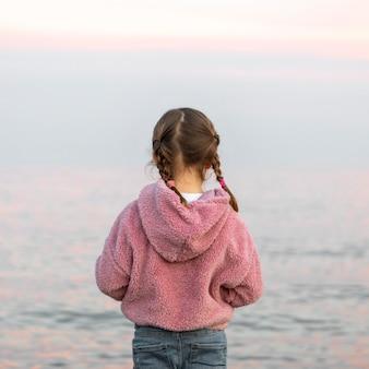 Fille de vue arrière au bord de la mer