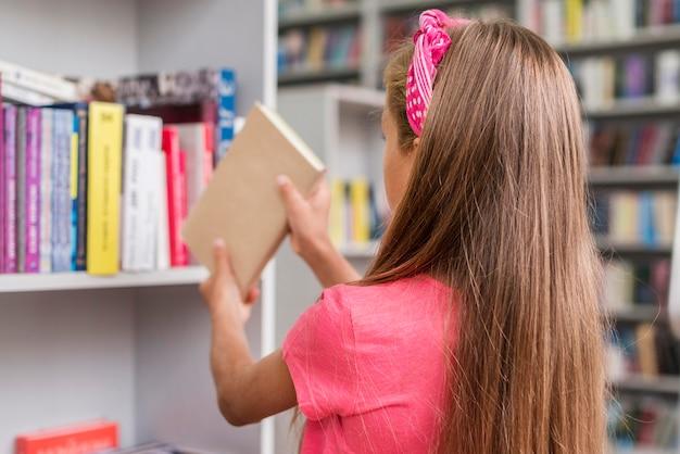 Fille de vue arrière remettant un livre sur l'étagère