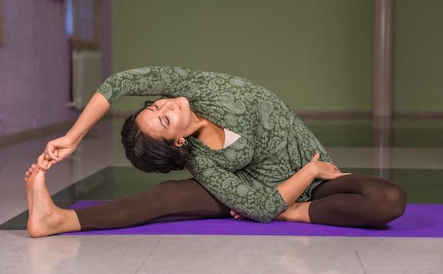Fille de yoga effectuant le yoga asana dans la salle de sport