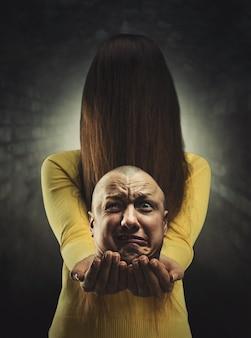 Fille zombie aux cheveux longs dans son visage en tenant une tête d'homme mort