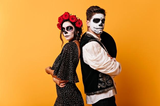 Fille zombie galbé en robe noire posant avec son petit ami. photo intérieure d'un beau couple avec un maquillage de crâne.