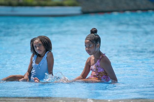 Filles africaines assis et jouant à l'eau dans la piscine du parc d'attractions.