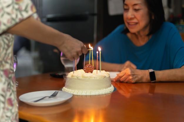 Les filles allument des bougies à la main sur un senior avec un autre gâteau d'anniversaire