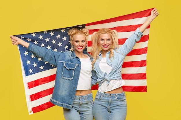 Filles américaines. heureux jeunes femmes en vêtements en denim tenant le drapeau des états-unis isolé sur fond jaune. fan de football