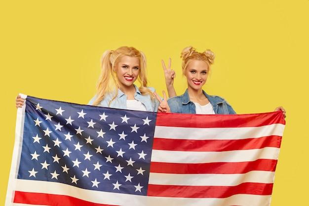 Filles américaines. heureux jeunes femmes en vêtements en jean tenant le drapeau des états-unis isolé sur fond jaune