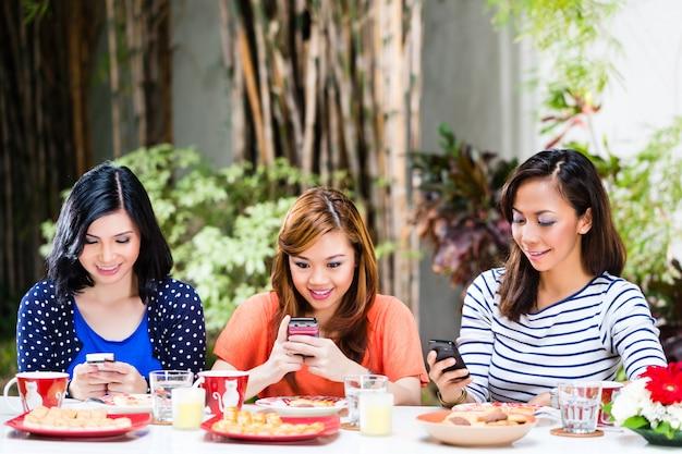 Filles asiatiques à l'aide de leurs téléphones mobiles
