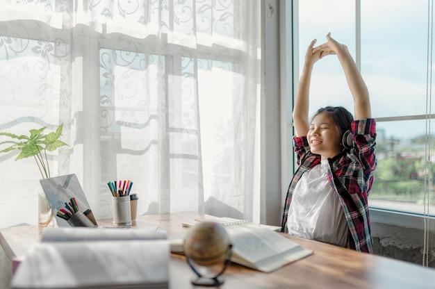 Les filles asiatiques étudient avec plaisir en ligne à la maison. utiliser des ordinateurs portables et des écouteurs comme outils pour faciliter l'apprentissage en ligne.