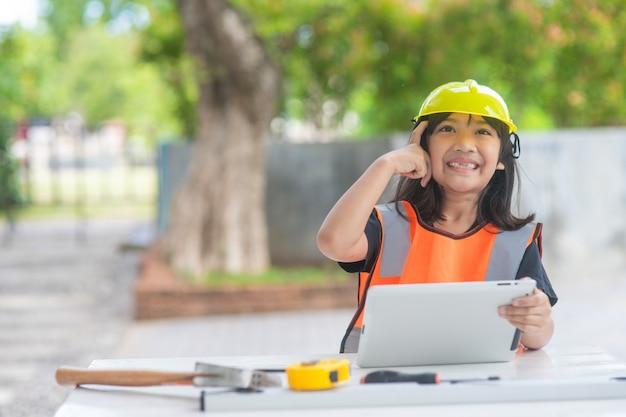 Les filles asiatiques jouant comme casque d'ingénieur sourient et sont heureuses le week-end.