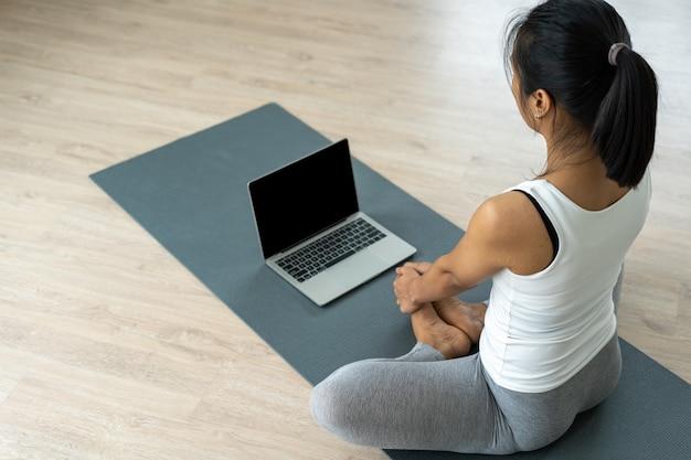 Les filles asiatiques minces font du yoga et regardent des didacticiels vidéo sur tablette.