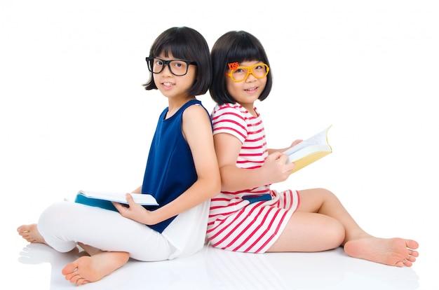 Filles asiatiques portant des lunettes assis sur le sol avec des livres