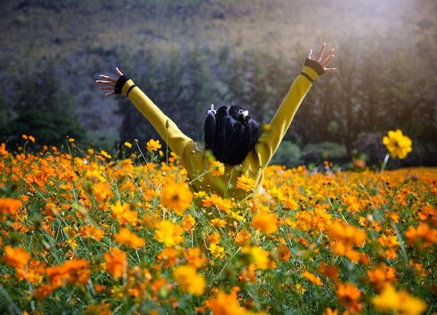 Les filles asiatiques sont heureuses dans le jardin de fleurs.