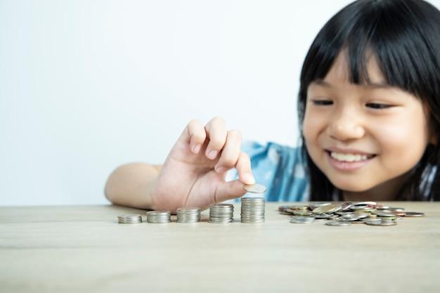 Les filles asiatiques sont heureuses d'organiser des pièces et de compter les pièces pour économiser de l'argent avec le mur blanc.