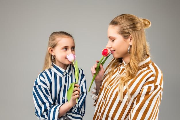 Filles assez attrayantes avec des cheveux clairs sentant le parfum des premières tulipes du printemps et en étant satisfaites
