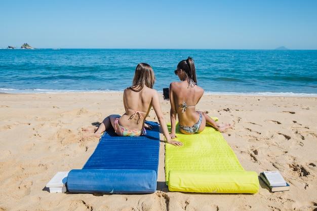 Filles assises près du rivage
