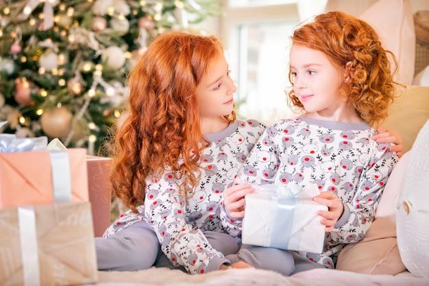 Les filles aux cheveux roux en pyjama sur le lit regardent des boîtes de cadeaux de noël contre le sapin de noël.