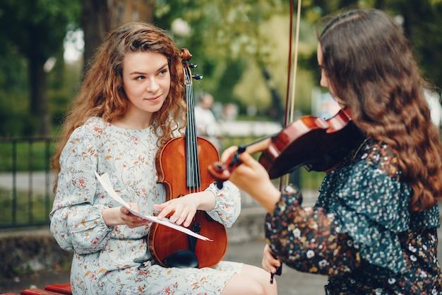 Filles belles et romantiques dans un parc avec un violon