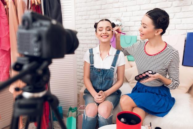 Les filles blogger tiennent les pinceaux et les ombres à paupières.