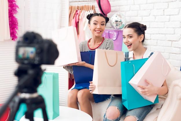Les filles bloggeuses tiennent des sacs colorés devant la caméra.