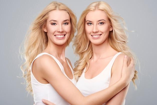 Filles blondes naturelles sur fond gris