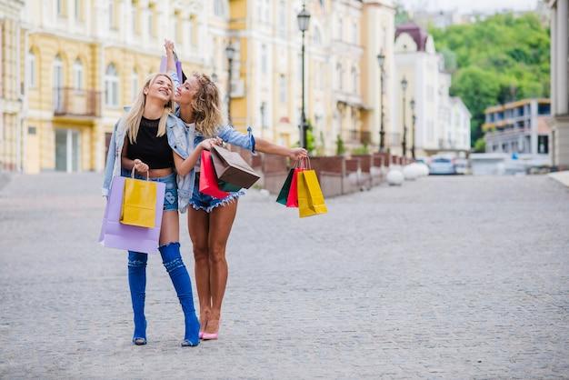 Filles blondes avec des sacs à provisions posant dehors