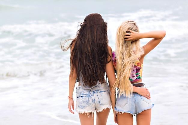 Filles bronzées avec de longues jambes debout près de l'océan et profitant d'une vue imprenable sur la nature. portrait en plein air de dames aux pieds nus en short en jean, passer la matinée en mer.