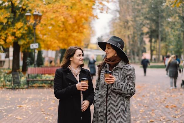 Filles buvant du café dans le parc