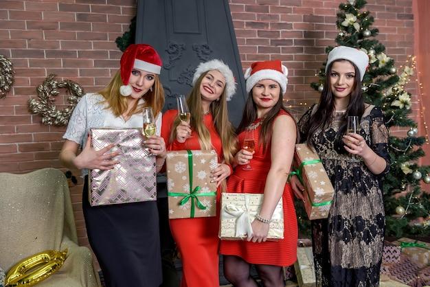 Filles avec champagne et coffrets cadeaux en fête