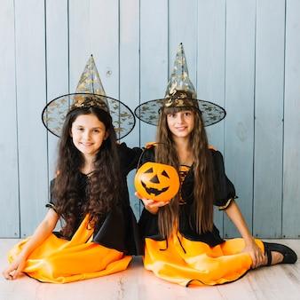 Filles en chapeaux pointus assis sur le sol avec un seau d'halloween