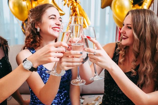 Filles chics célébrant la fête d'anniversaire. mesdames en robes assises ensemble, tintant des verres de champagne, s'amusant.