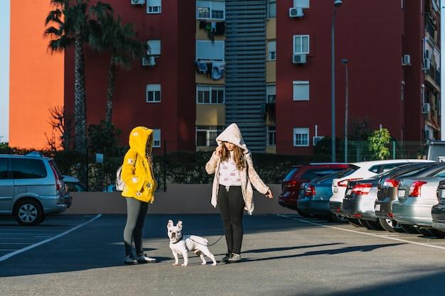 Filles avec un chien qui marche sur le parking