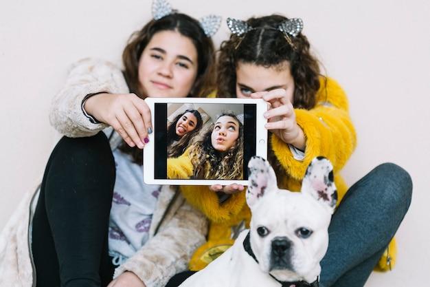 Filles avec un chien et une tablette