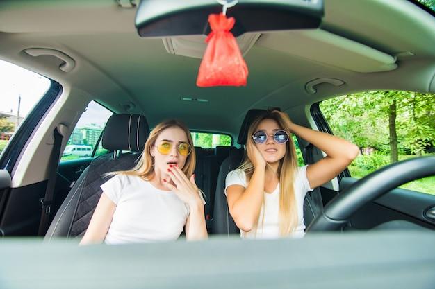 Filles choquées en conduisant une voiture. vacances d'été
