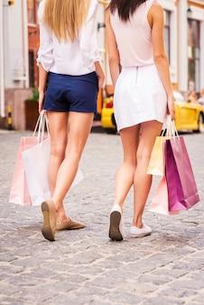 Filles commerçantes. vue arrière de deux belles jeunes femmes portant des sacs à provisions en marchant le long de la rue