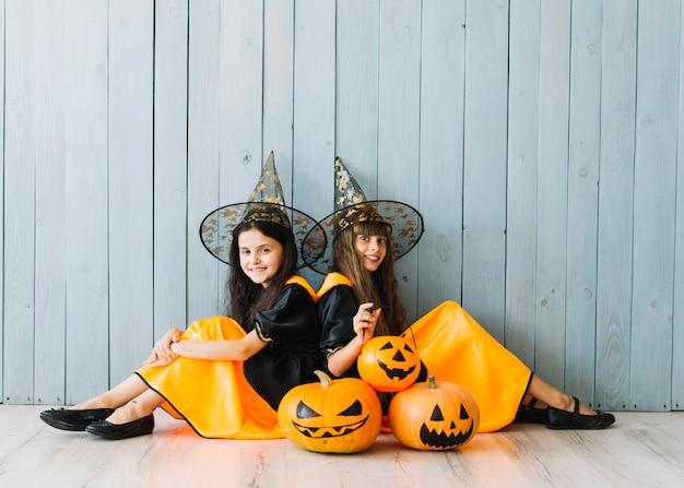 Filles en costume de sorcière et chapeaux pointus assis sur le sol avec des citrouilles