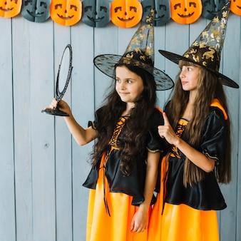 Filles avec des costumes et des chapeaux pointus regardant dans le miroir